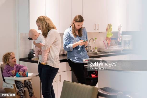 Caucasian mothers and daughters in kitchen