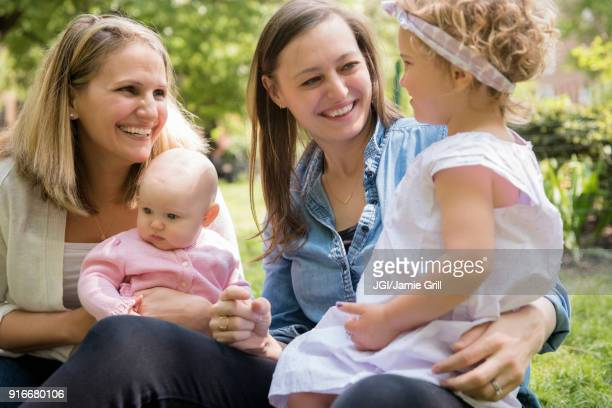 Caucasian mothers and daughters smiling in park