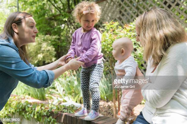 Caucasian mothers holding daughters on garden wall