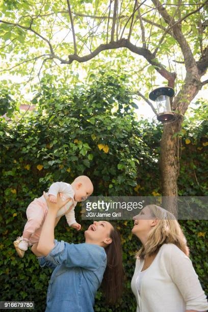 Caucasian mothers lifting baby daughter under tree