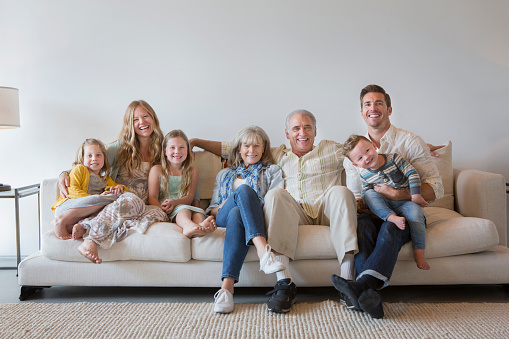 Caucasian multi-generation family sitting on sofa in living room - gettyimageskorea