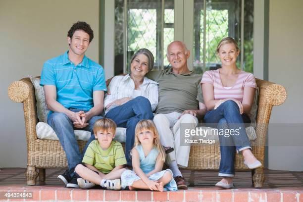 caucasian multi-generation family smiling on porch - banco asiento fotografías e imágenes de stock