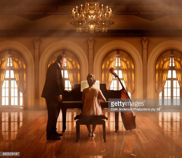 Caucasian music teacher and student at piano in ballroom