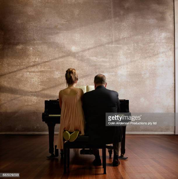 Caucasian music teacher and student playing piano