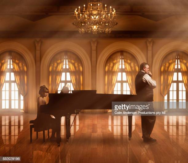Caucasian music teacher listening to student at piano in ballroom
