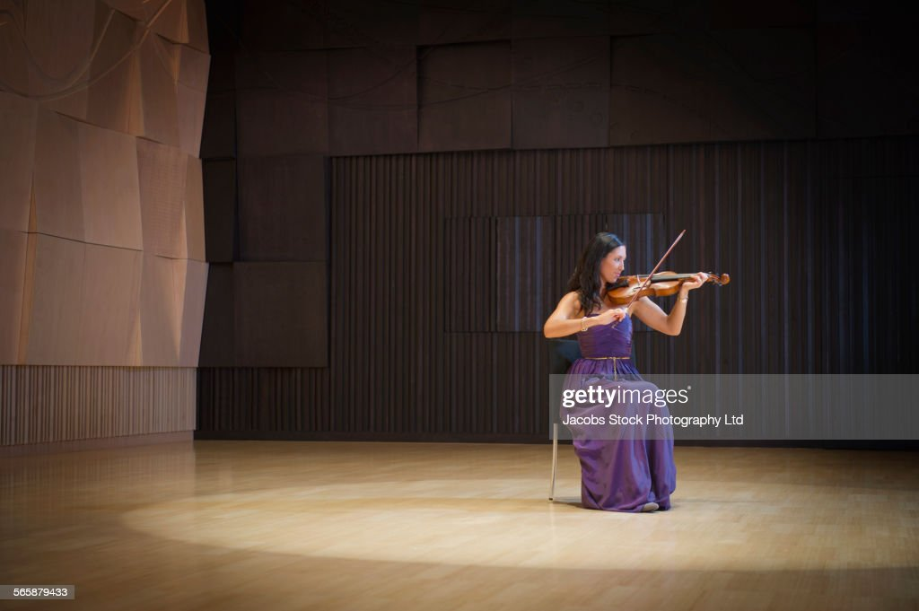 Caucasian musician playing violin on stage : Stock Photo