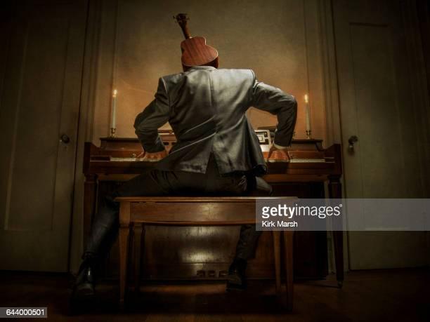 Caucasian musician with ukulele head playing piano