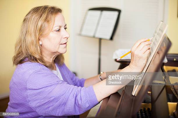 Caucasian musician writing sheet music at piano