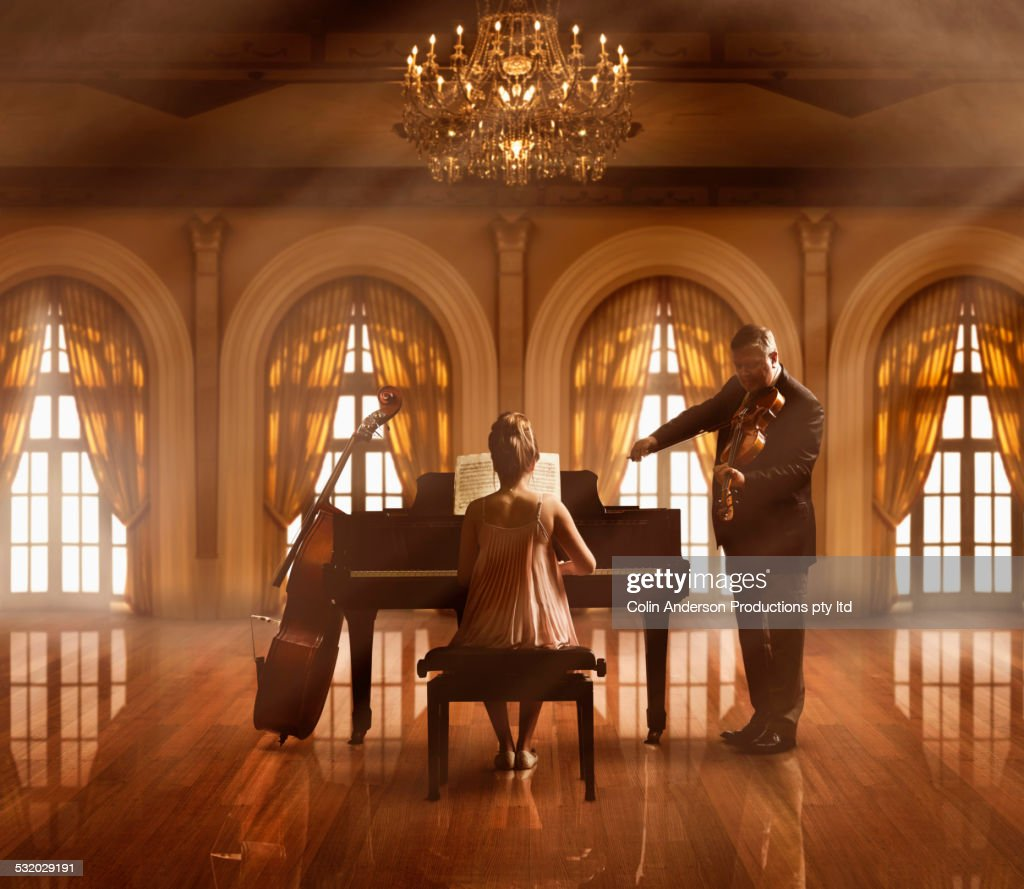 Caucasian musicians playing piano and violin : Stock Photo