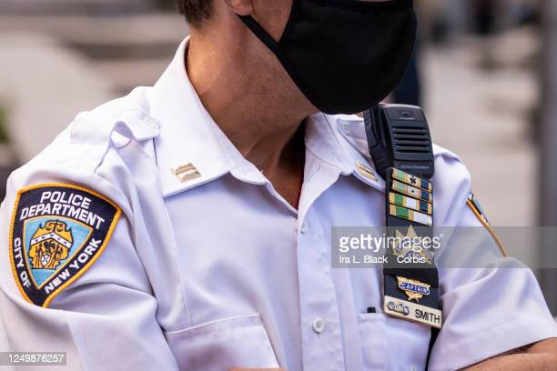 Caucasian New York Police Department officer wearing a mask has his badge number covered up with a black strip of fabric in Columbus Circle....