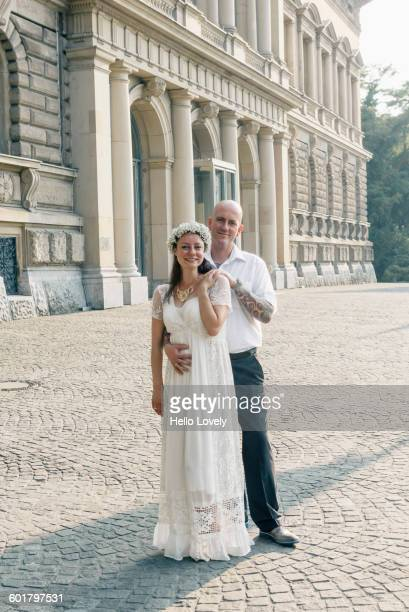 Caucasian newlywed couple hugging outdoors