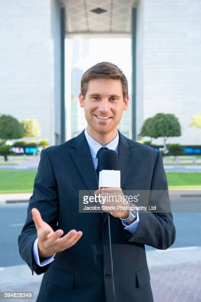 Caucasian news anchor talking with microphone