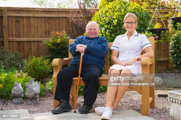 caucasian nurse and patient sitting in garden - spalding england stock photos and pictures