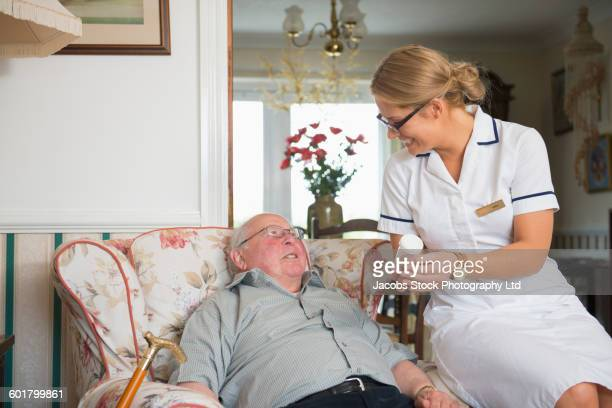 Caucasian nurse and patient talking in home