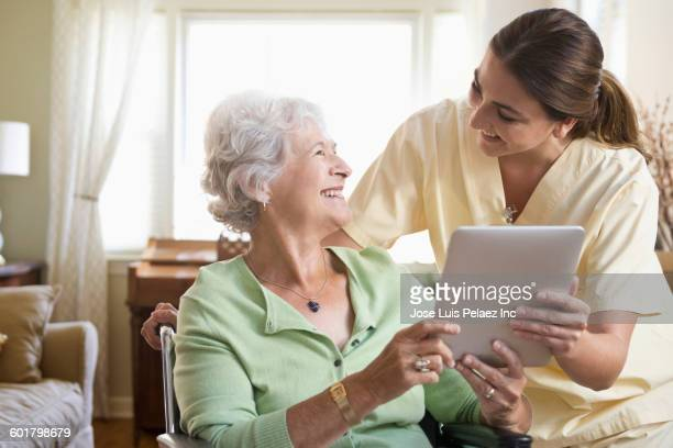 Caucasian nurse and patient using digital tablet