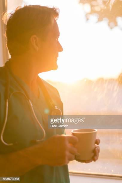 Caucasian nurse drinking cup of coffee at window