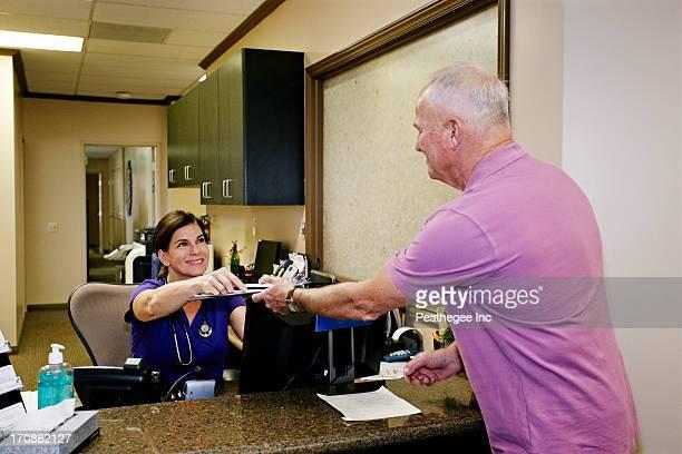 Caucasian nurse handing clipboard to patient