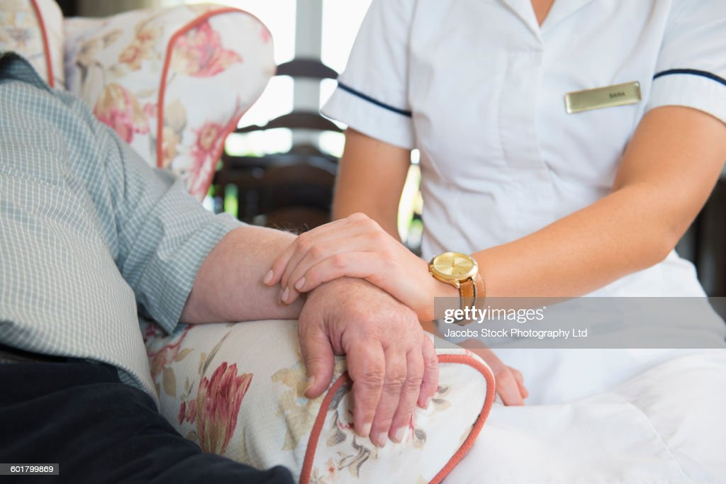 Caucasian nurse measuring pulse of patient in home : Stock Photo