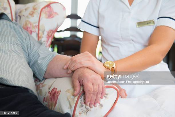 caucasian nurse measuring pulse of patient in home - social services stock photos and pictures