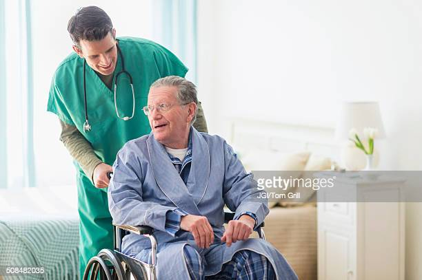 caucasian nurse wheeling patient in home - leaning disability stock pictures, royalty-free photos & images