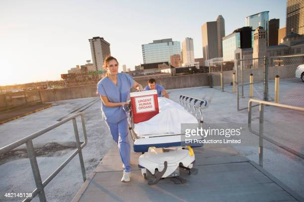 Caucasian nurses rushing organs and patient on rooftop