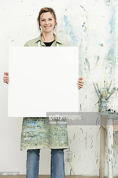Caucasian painter holding blank canvas in studio