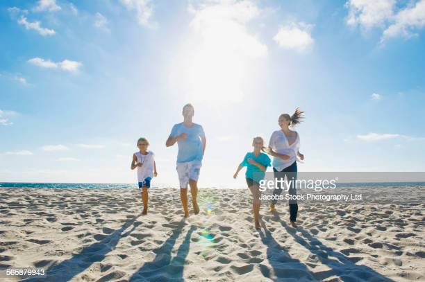 Caucasian parents and children running on beach