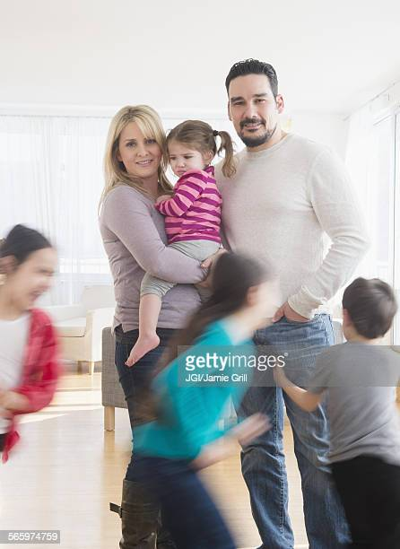 Caucasian parents busy with running children