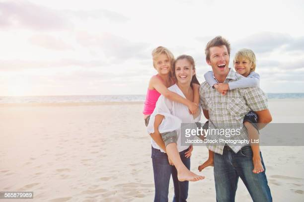 Caucasian parents carrying children piggyback on beach