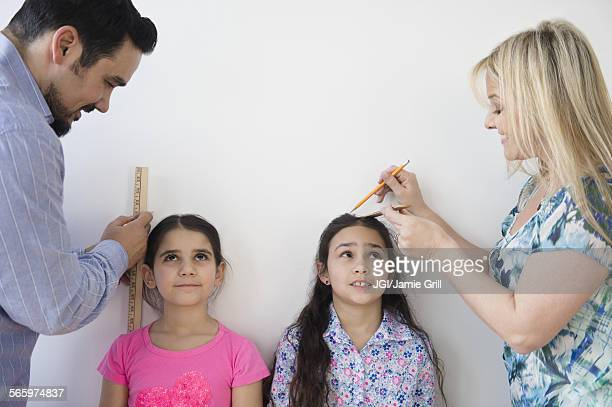 Caucasian parents measuring height of daughters on wall