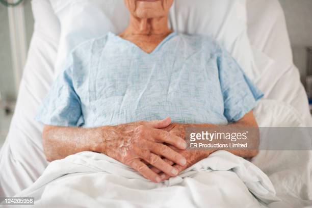 caucasian patient in hospital bed with hands clasped - old woman in sick bed stock photos and pictures