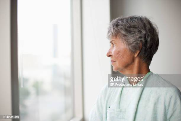 caucasian patient looking out hospital window - introspection stock pictures, royalty-free photos & images