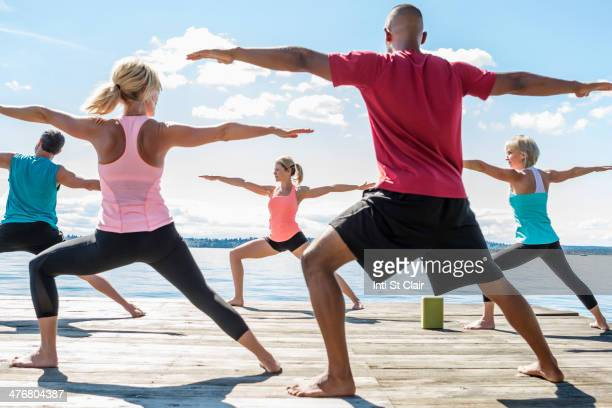 Caucasian people practicing yoga on wooden dock