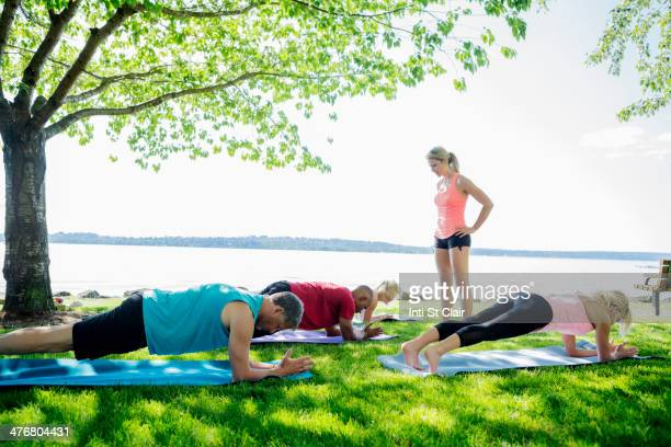 Caucasian people practicing yoga outdoors