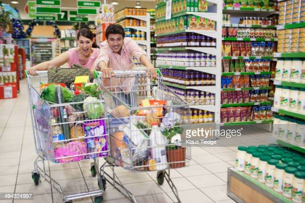 Caucasian people racing each other at grocery store