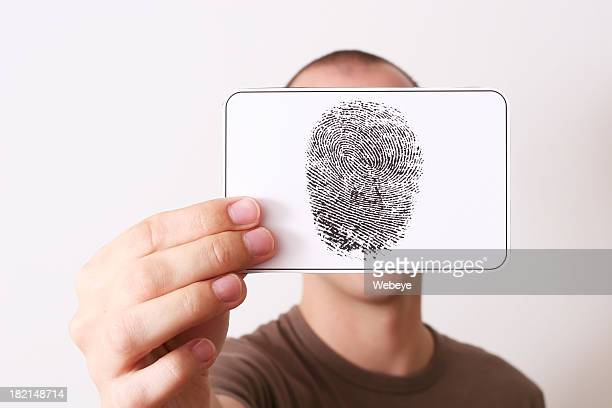 Caucasian person holding up ink fingerprint over face