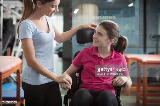 caucasian physical therapist comforting girl in wheelchair - sezione centrale foto e immagini stock