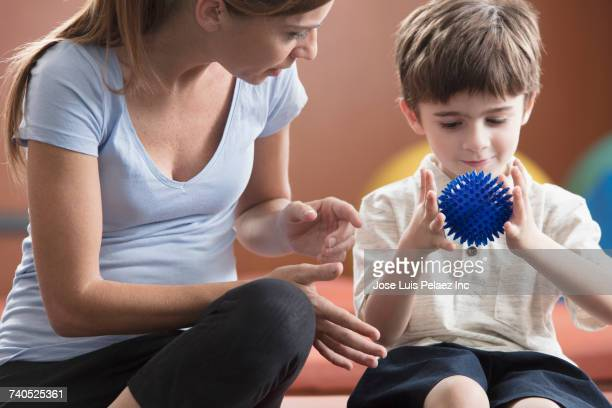 Caucasian physical therapist watching boy squeezing ball