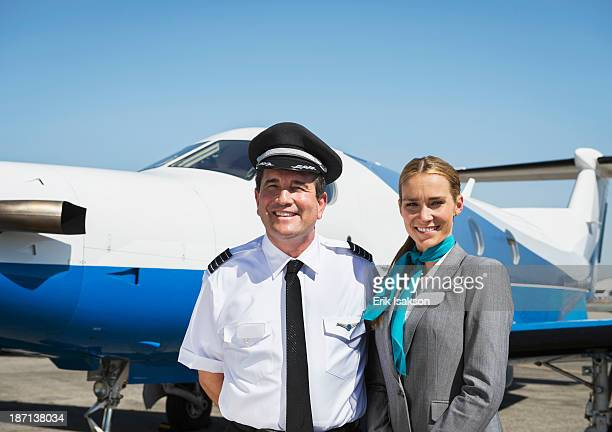Caucasian pilot and flight attendant smiling on runway