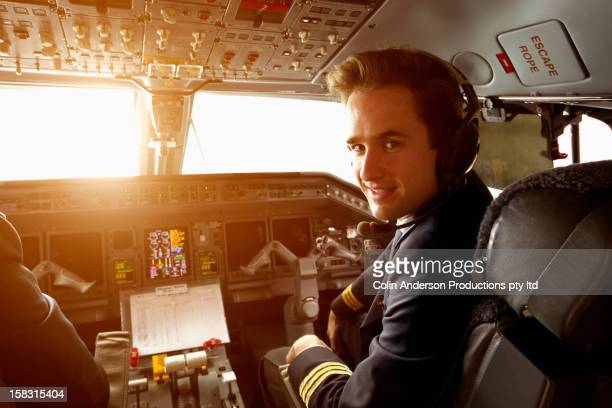 Caucasian pilot flying jet at sunset