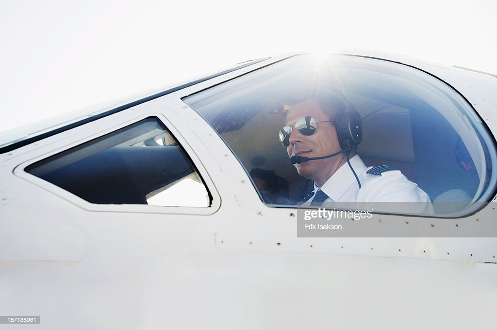 Caucasian pilot in airplane cockpit : Stock Photo