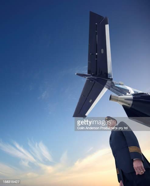 caucasian pilot standing underneath airplane - flugzeugheck stock-fotos und bilder