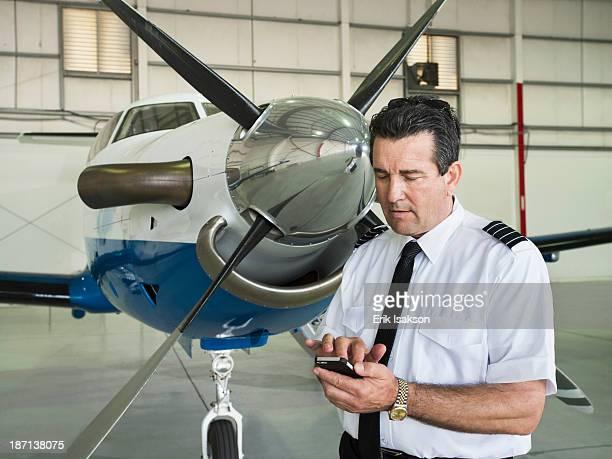 Caucasian pilot using cell phone in hangar