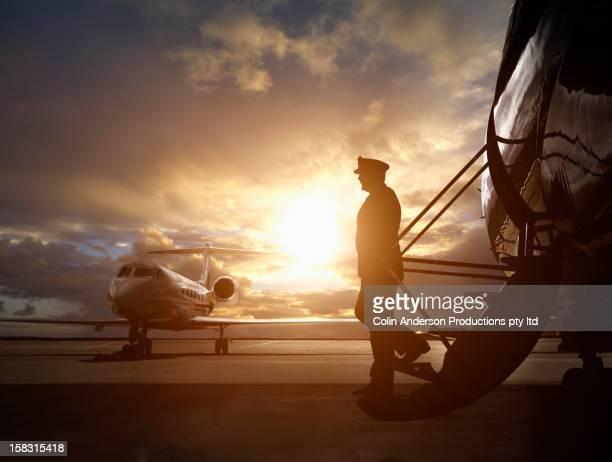 Caucasian pilot walking down steps of jet