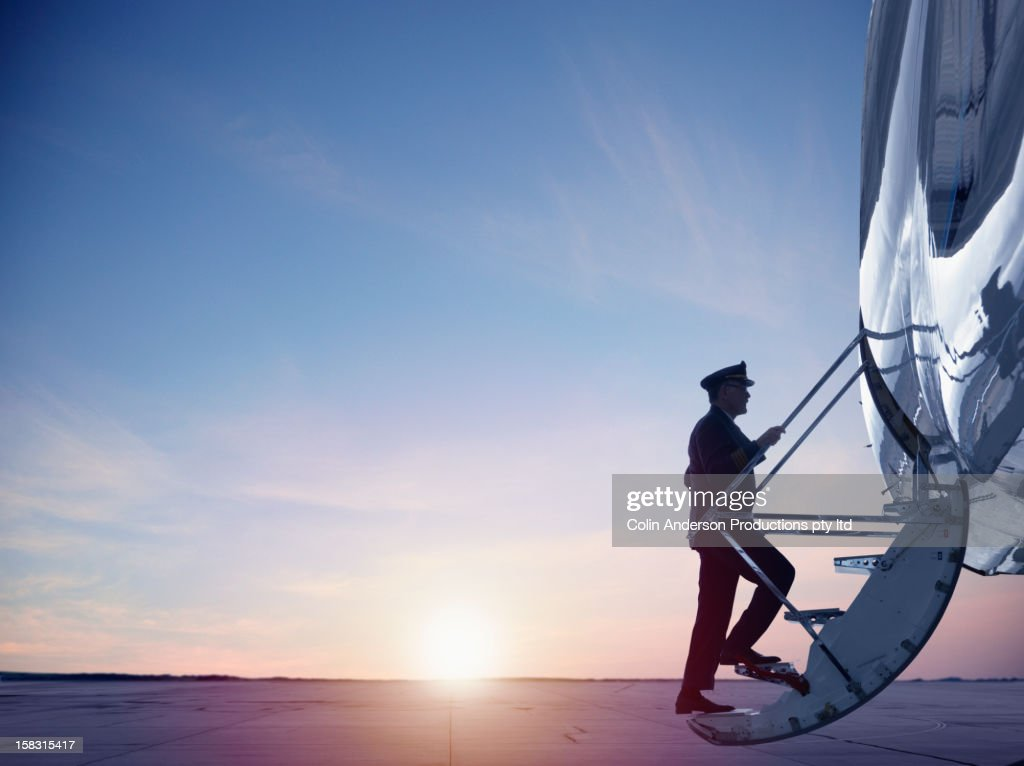 Caucasian pilot walking up steps of jet : Stock Photo