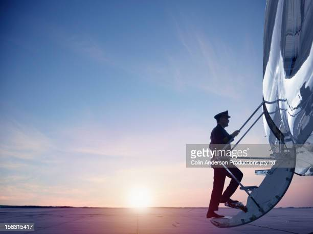 Caucasian pilot walking up steps of jet