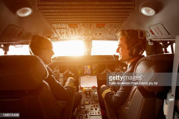 Caucasian pilots flying jet at sunset