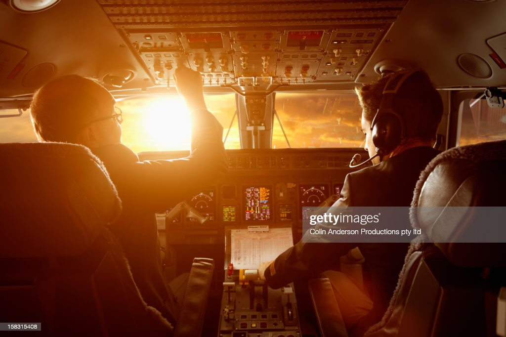 Caucasian pilots flying jet at sunset : Stock Photo