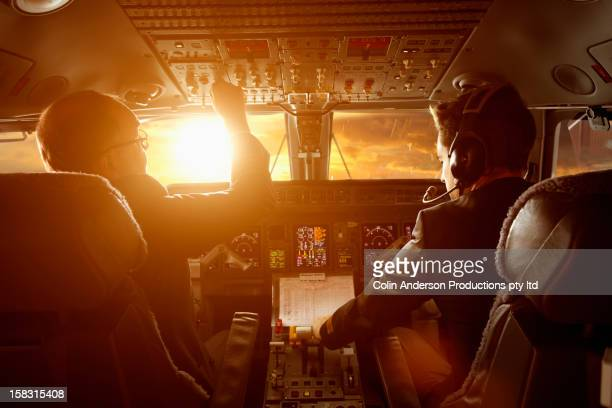 Caucasian pilots flying jet at sunset