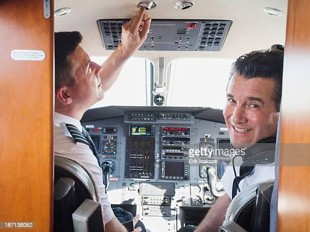 Caucasian pilots in airplane cockpit